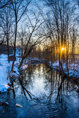 Sunset over a creek in a snow covered forest, near Abbottstown, — Stock Photo