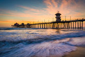Waves in the Pacific Ocean and the pier at sunset, in Huntington — Stock Photo