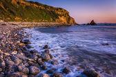 Long exposure of waves crashing on rocks at sunset, taken at Pel — Stock Photo