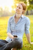Woman Enjoys Music in a Park at Sunset — Stock Photo