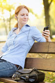 Woman Picking a Song on a Smartphone — Stockfoto