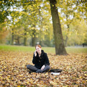 Woman Calling by Phone from an Autumn Park — Stockfoto