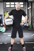 Well trained man with med-ball at the gym — Stock Photo