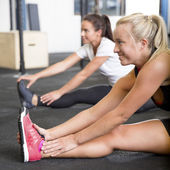 Two smiling women stretching on the floor — Stock Photo