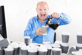 Happy businessman drinks way too much coffee — Stock Photo