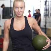 Smiling young woman with slam ball at gym center — Stock fotografie