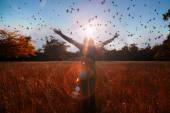 Young girl spreading hands with joy and inspiration facing the sun,sun greeting,freedom concept,bird flying above sign of freedom and liberty — Stock Photo