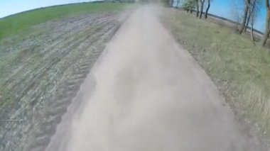 Driving on rural dusty road. The camera is outside and aimed back. — Stok video