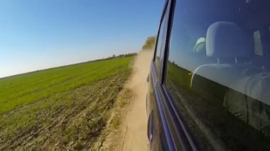 Fast driving a car in the countryside. The camera is outside and aimed back. — Stock Video