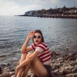Pin up young beautiful girl on the sea in short jeans and striped T-shirt with long hair rocks glasses gulls water clouds, wave, dream figure with glasses emotions, smile with teeth, open mouth — Stock Photo #60642781