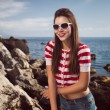 Pin up young beautiful girl on the sea in short jeans and striped T-shirt with long hair rocks glasses gulls water clouds, wave, dream figure with glasses emotions, smile with teeth, open mouth — Stock Photo #60643211