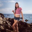 Pin up young beautiful girl on the sea in short jeans and striped T-shirt with long hair rocks glasses gulls water clouds, wave, dream figure with glasses emotions, smile with teeth, open mouth — Stock Photo #60643221