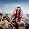 Pin up young beautiful girl on the sea in short jeans and striped T-shirt with long hair rocks glasses gulls water clouds, wave, dream figure with glasses emotions, smile with teeth, open mouth — Stock Photo #60643241