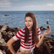 Pin up young beautiful girl on the sea in short jeans and striped T-shirt with long hair rocks glasses gulls water clouds, wave, dream figure with glasses emotions, smile with teeth, open mouth — Stock Photo #60643401