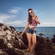 Pin up young beautiful girl on the sea in short jeans and striped T-shirt with long hair rocks glasses gulls water clouds, wave, dream figure with glasses emotions, smile with teeth, open mouth — Stock Photo #60643455