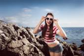 Pin up young beautiful girl on the sea in short jeans and striped T-shirt with long hair rocks glasses gulls water clouds, wave, dream figure with glasses emotions, smile with teeth, open mouth — Stock Photo