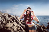 Pin up young beautiful girl on the sea in short jeans and striped T-shirt with long hair rocks glasses gulls water clouds, wave, dream figure with glasses emotions, smile with teeth, open mouth — Stok fotoğraf