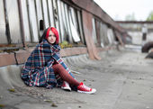 A teenage girl is sitting on the roof covered with a rug — Stock Photo