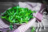 Arugula salad on wooden background — Stockfoto