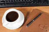Office desk with coffee cup — Stock Photo