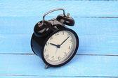 Klassisk väckarklocka på blå trä bakgrund. — Stockfoto
