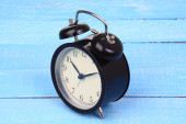 Classic alarm clock on blue wood background. — Stock Photo