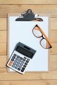 Clip board with calculator on wood background — Stock Photo