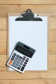 Clip board with calculator on wood background — 图库照片