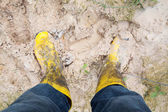 Yelkow Muddy rubber boots on wet silt — Stock Photo