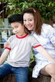 Asian woman talking about with your son in the park — Stock Photo