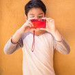 Portrait of asian cute little boy holding red camera — Stock Photo #64571937