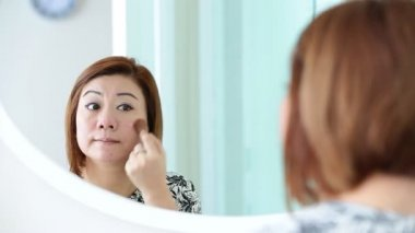 Asian woman applying makeup and looking at mirror in bedroom. — Stock Video