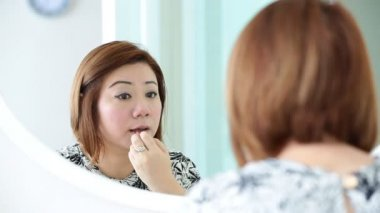 Asian woman applying makeup and looking at mirror in bedroom. — ストックビデオ