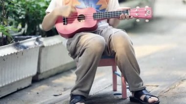 Little asian child sitting on mini chair and playing guitar — Stock Video