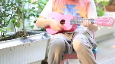 Little asian child sitting on mini chair and playing guitar — Stockvideo