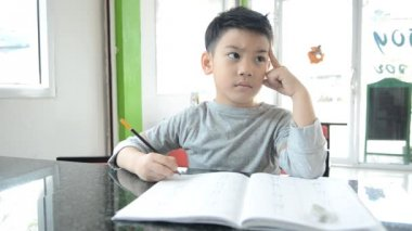 An asian boy doing his homework — Stockvideo
