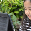 Little Asian girl playing tablet on the table — Stock Video #71156199