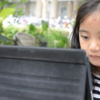 Little Asian girl playing tablet on the table — Stock Video #71157211
