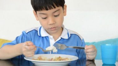 Little asian boy eating fried rice and playing tablet computer . — Stock video