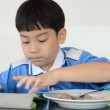 Little asian boy eating fried rice and playing tablet computer . — Stock Video #71240009