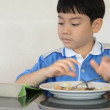 Little asian boy eating fried rice and playing tablet computer . — Stock Video #71241607