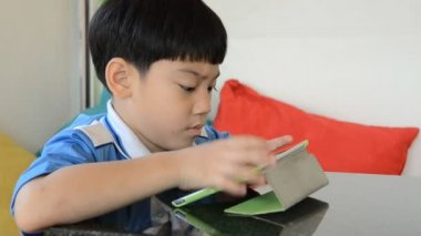 Little asian boy smiles and playing tablet computer acting on his face — Stock Video