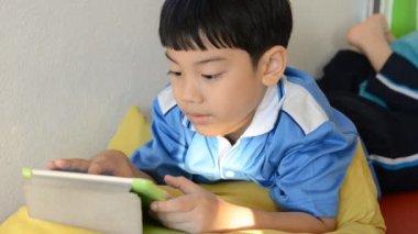 Weinig Aziatische jongen glimlacht en spelen tablet pc op zijn gezicht — Stockvideo