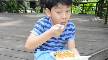 Young asian cute boy eating fried chiness noodles.,in foam box — Stock Video
