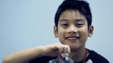 Little asian boy drinks water from a bottle — Stock Video