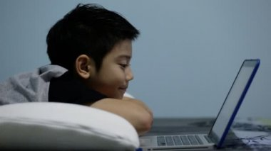 Asian cute boy watching and smile games on laptop computer. — Stock Video