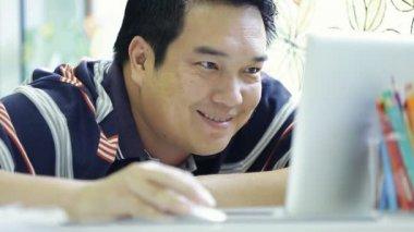 Szczęśliwy człowiek azji za pomocą jego laptop i uśmiech — Wideo stockowe
