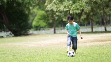 Jonge Aziatische jongen te voetballen in een park, Bangkok Thailand — Stockvideo