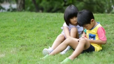 Little asian boy and girl blowing soap bubble in the park — Stock Video