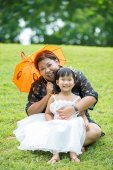 Little asian girl playing on green grass with her mother — Stock Photo